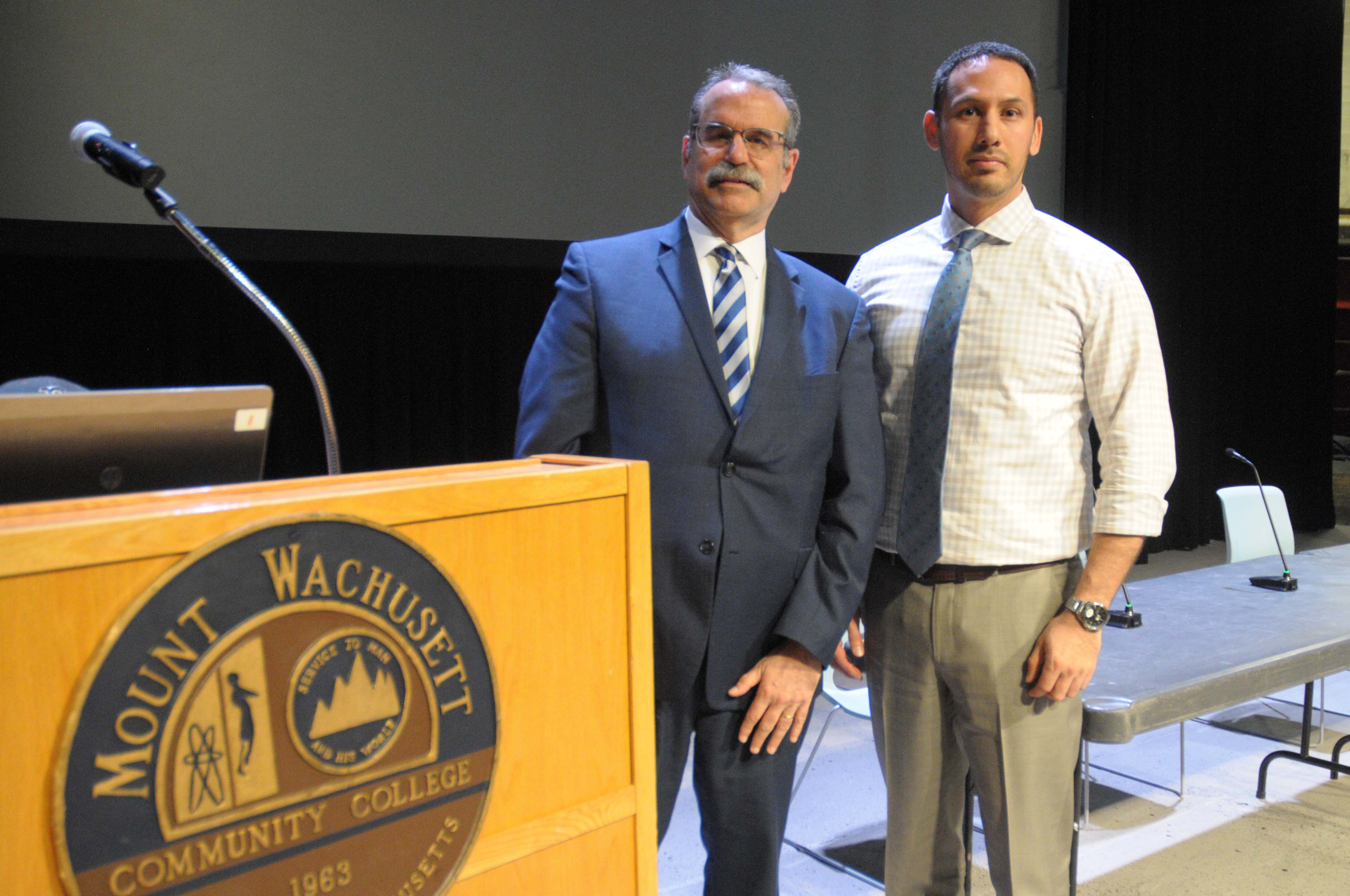 Two men stand together next to a podium.